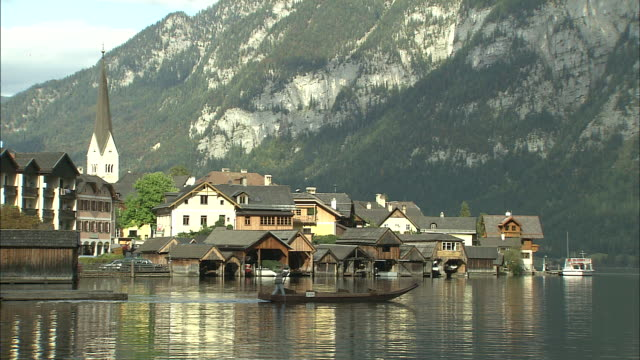 Man paddles boat across Hallstattersee away from lakeside buildings and church with mountains in background, Hallstatt