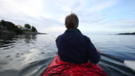 Man paddles kayak through calm waters of ocean bay