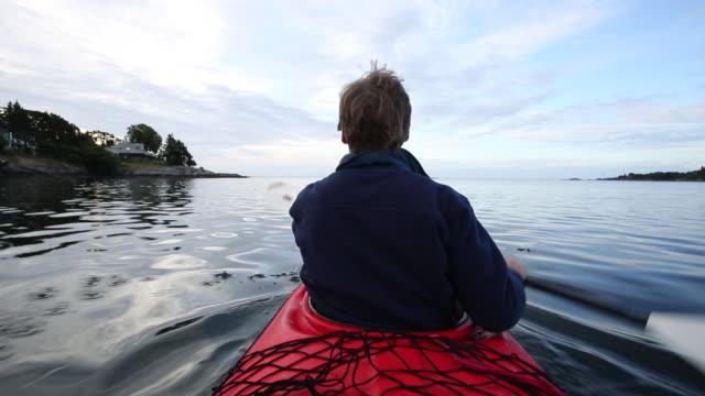 Man paddles kayak through calm waters of ocean bay
