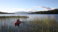 Man paddles kayak through marsh, sunrise