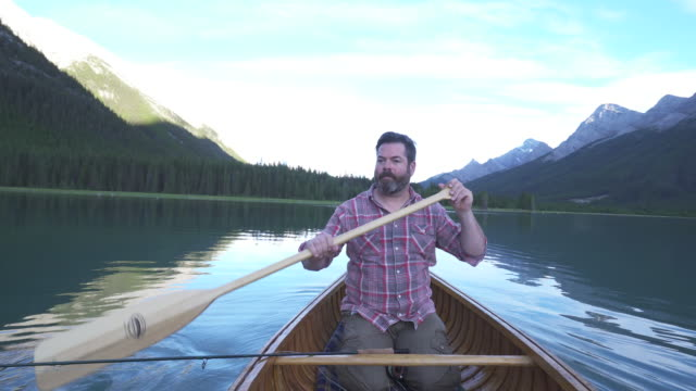 Man paddles wooden canoe into mountain lake, with fishing gear