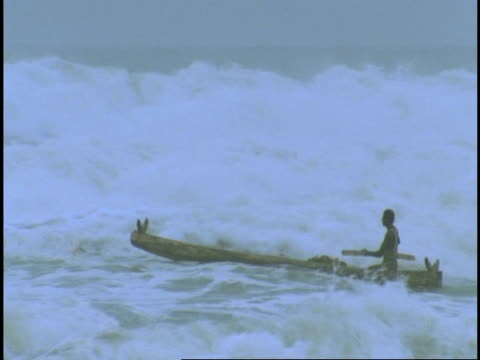MS man paddling dugout canoe through large surf, Western Ghats, India