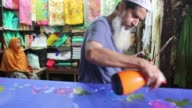 A man paintig on the fabric at a workshop on April 3 2016 in Dhaka Bangladesh The local boutique shops and fashion houses have been adorned with...