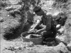 B/W 1927 man panning for gold in bucket of water / Nevada / newsreel