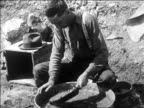 B/W 1927 man panning for gold over bucket of water / Nevada / newsreel