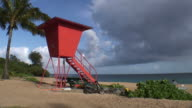 (HD1080i) Man Passes Tropical Orange Lifeguard Tower