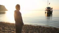 Man pauses at beach edge at sunrise, contemplative