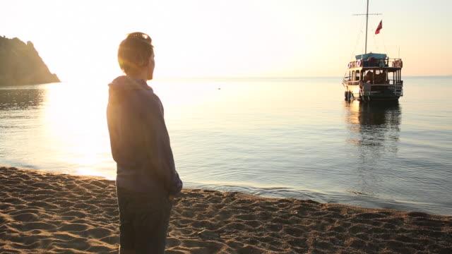 Man pauses at beach edge at sunrise, contemplative