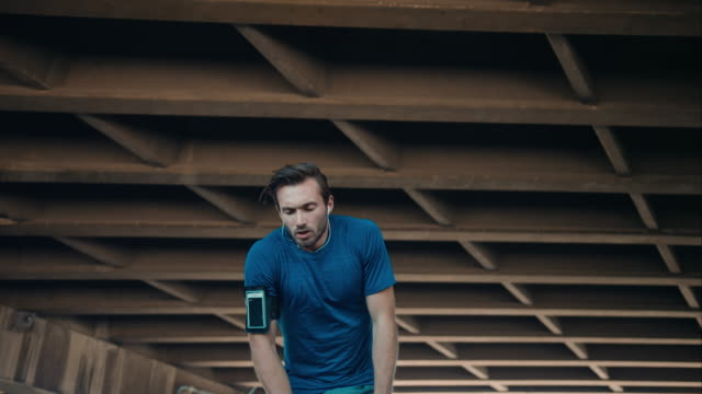 Man pauses jogging in urban setting