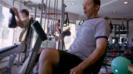 MS, man pedaling on exercise bike then rubbing knee, USA, Pennsylvania, Solebury,