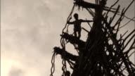 Man peers off wooden tower during land diving ritual, Pentecost, Vanuatu