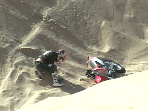 ZO, ZI, PAN, COMPOSITE, SHAKY, CU,  Man performing jump on motorbike then crashing, medical staff attending to him, Imperial Sand Dunes. California, USA