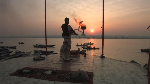 WS, Man performing Puja ritual by Ganges river at sunrise, Varanasi, Uttar Pradesh, India