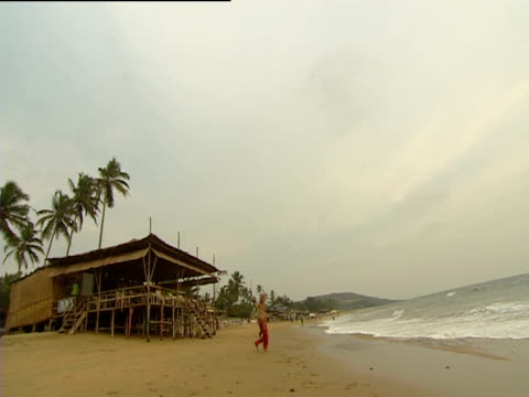 Man performs with twirling batton on the beach Goa