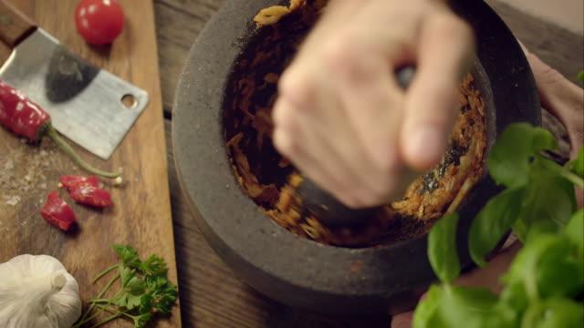 Mann pestling Knoblauch in einem Stößel