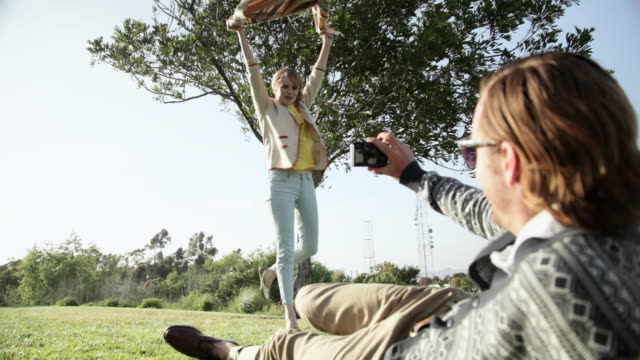 Man photographing girlfriend as she shakes out blanket