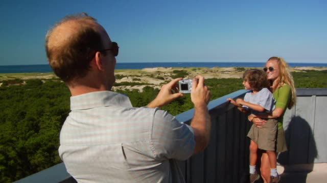 MS, Man photographing wife and son (4-5) on beach, Provincetown, Massachusetts, USA