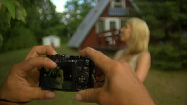 SELECTIVE FOCUS, CU, Man photographing woman in front of holiday house, Fish Creek, Wisconsin, USA