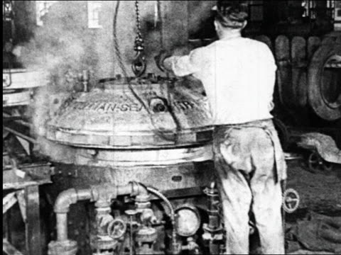 B/W 1925 man placing chain on steaming machine in Goodyear tire factory / industrial
