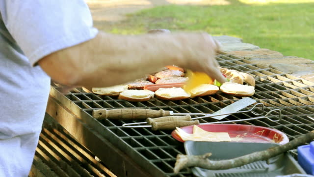 Man placing cheese on barbecue burgers