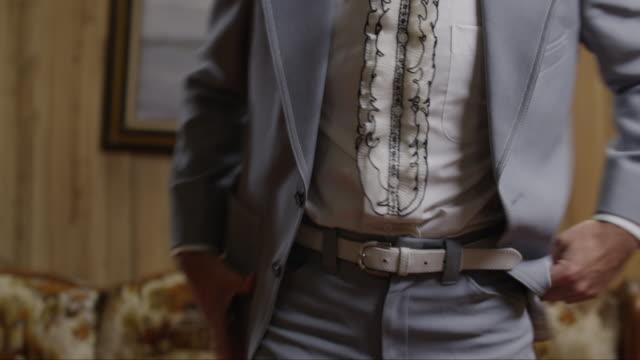 CU TD Man placing hands on his buttocks, adjusting suit turning around in living room / Orem, Utah, USA