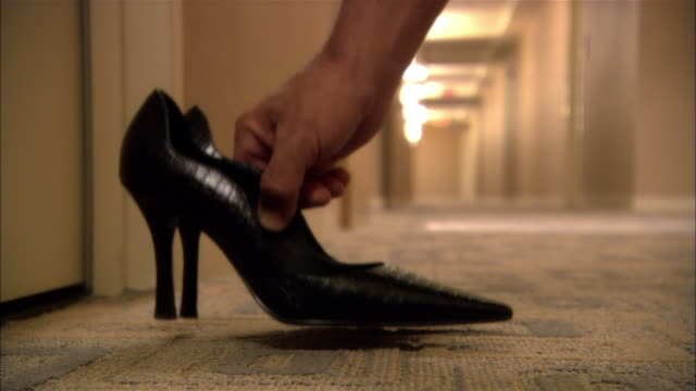 CU, Man placing pair of women's high heeled shoes outside hotel door