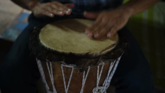 Man playing a wooden drum.