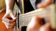 man playing acoustic guitar in picking finger style - close up view