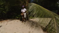 MS Man playing African drum on the beach / Brightown, Barbados