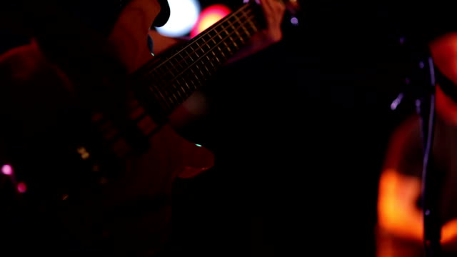 Man Playing Bass Guitar at Concert in Local Bar