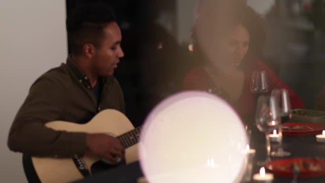Man playing guitar at a dinner party