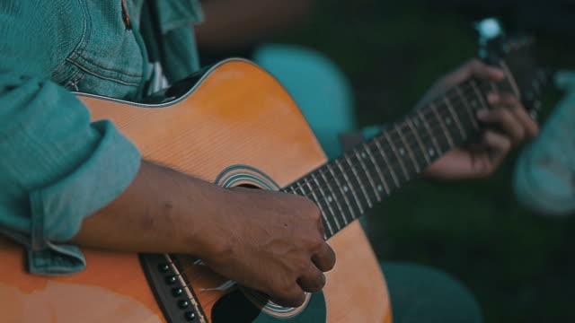 man spelen gitaar close-up, buiten
