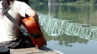 Man Playing Guitar on Boat Dock