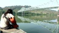 Man Playing Guitar on Dock By Bridge