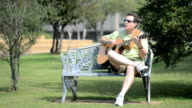 Man Playing Guitar on Park Bench