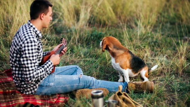 Man playing ukulele on camping to his beagle dog