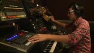 MS man playing various keyboards in recording studio, Gent, Belgium