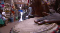 A man plays a djembe drum in a market. Available in HD