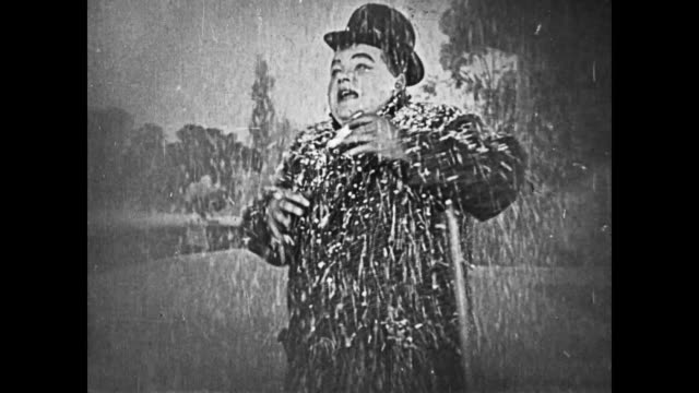 Fatty Arbuckle plays a harmonica, distracted by the stream of fake snow that a stagehand pours on him
