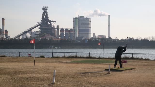A man plays golf as smoke rises into the sky from the stacks of a Posco steel mill in Pohang South Korea on Saturday Jan 21 People walk along a golf...