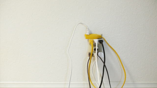 MS, Man plugging cord into an overloaded electrical outlet