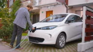 DS Man plugging in electric car at home