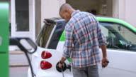 SLO MO Man plugging in his car at charging station
