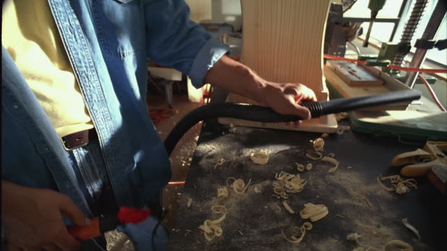 MS ZI ZO SLO MO Man plugging plug into extension cord and vacuuming off work table / Austin, Texas, USA
