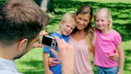 A man points a camera at his family who hold each other before they turn to the camera and smile