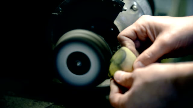 Man polishing heart-shaped metal