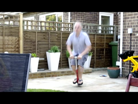 / man possibly drunk fooling around with pogo stick / man jumps a few times and then falls on ground dislocating his finger / woman tries to help man...