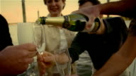 Man pouring champagne overflowing from bottle into champagne flutes for men and woman on dock