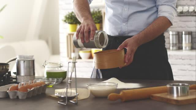 Mann gießen Mehl aus dem Krug in Mehl-Streudose