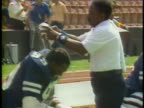 1983 MS ZI Man pouring water on Orlando Renegades football player to cool him off during game / USA